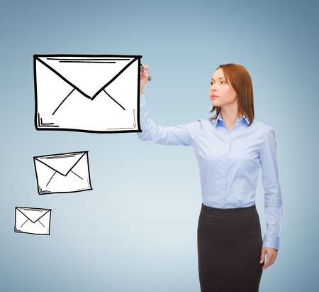 office, business and new technology concept - smiling businesswoman drawing envelope on virtual screen photo