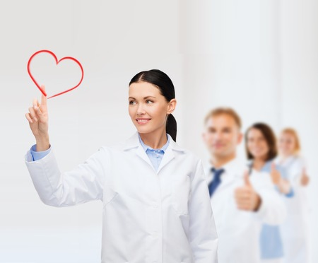 healthcare, medicine and technology concept - smiling female doctor pointing to heart Stock Photo - 26175906