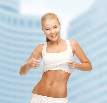 6 pack: fitness and diet concept - beautiful sporty woman showing thumbs up and her abs
