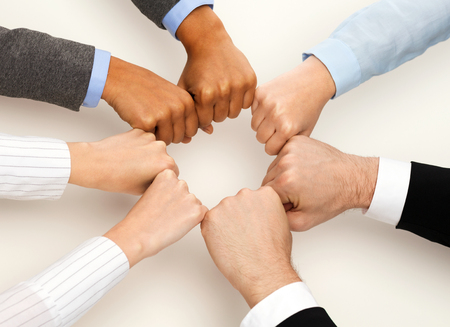 international business agreement: business and teamwork concept - closeup of businesspeople hands in fists in circle Stock Photo