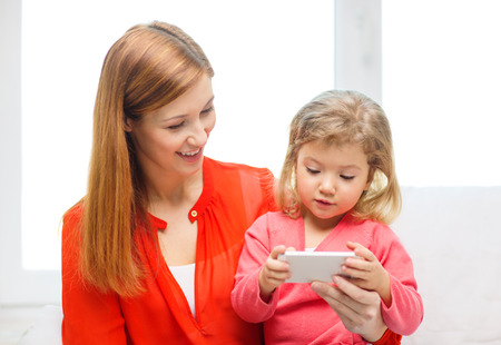 family, children, parenthood, technology and internet concept - happy mother and daughter with smartphone at home photo
