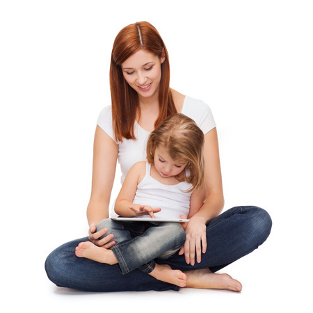 childhood, parenting and technology concept - happy mother with adorable little girl and tablet pc computer Stock Photo