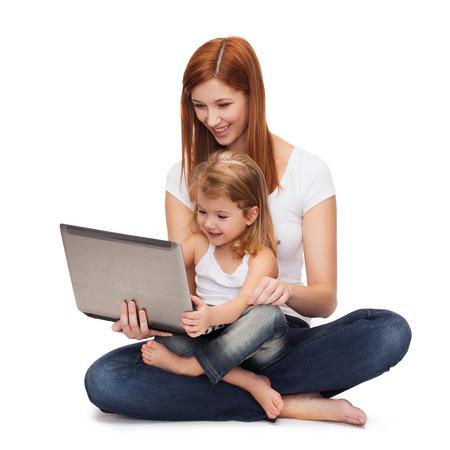 niños jugando videojuegos: la infancia, la paternidad y el concepto de la tecnología - la madre feliz con adorable niña con ordenador portátil