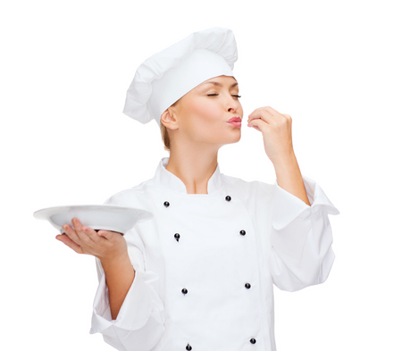 cooking and food concept - smiling female chef, cook or baker with empty plate showing delicious sign photo