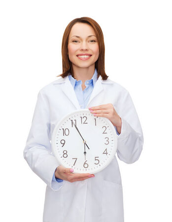 healthcare and medicine concept - smiling female doctor with wall clock photo