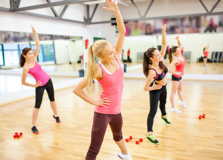 group fitness: fitness, sport, training, gym and lifestyle concept - group of smiling women stretching in the gym