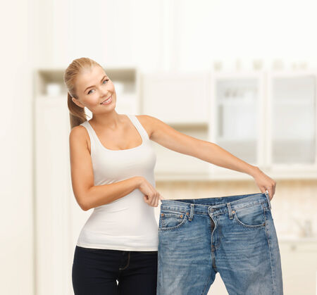 fitness, diet and good shape concept - sporty woman showing big pants photo
