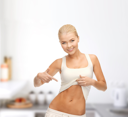 fitness and diet concept - beautiful sporty woman pointing at her abs photo