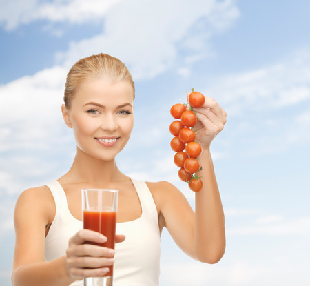 fitness and diet concept - young woman holding glass of juice and tomatoes photo