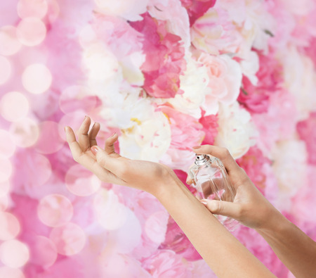 cosmetics, body parts and beauty concept - close up of woman hands spraying perfume photo