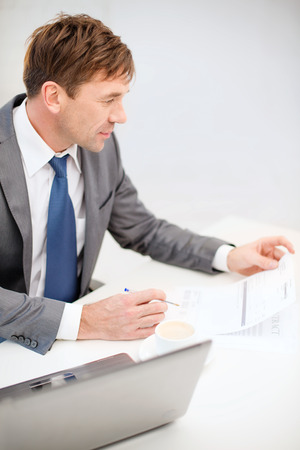 technology, business, internet and office concept - handsome businessman working with laptop computer, coffee and documents Stock Photo - 26176181