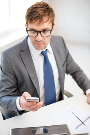 technology, business, internet and office concept - handsome businessman working with laptop computer and smartphone Stock Photo - 26176183