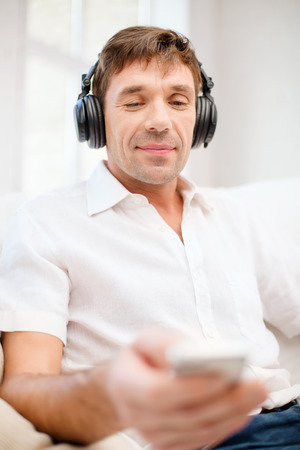 technology, leisure and lifestyle concept - happy man with headphones listening to music at home Stock Photo - 26176185