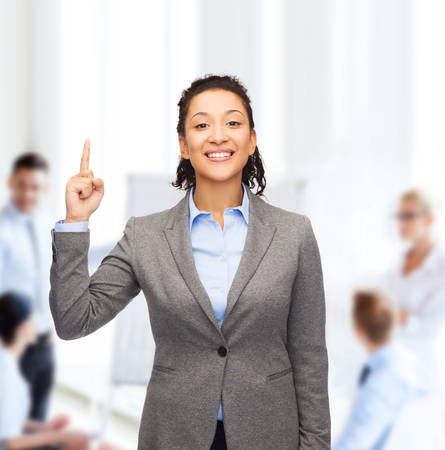 business and advertisement concept - attractive young woman with her finger up at office photo