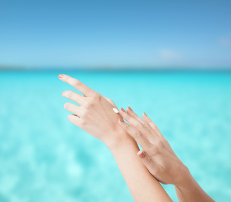 handcare: body parts, conspetics and spa concept - close up of female soft skin hands with creme