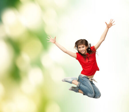 youth and fitness concept - happy girl jumping in the air photo