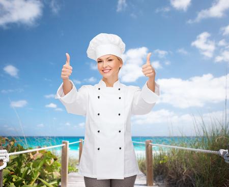 Cocinar, el gesto y el concepto de la comida - sonriendo mujer chef, cocinero o baker mostrando los pulgares para arriba Foto de archivo - 26175688