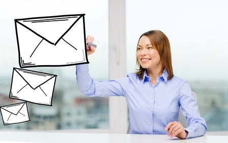 office, business, technology concept - businesswoman drawing envelope on virtual screen photo