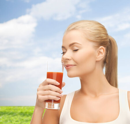 health and diet concept - close up of young woman drinking tomato juice photo