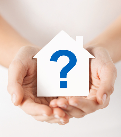 real estate and family home concept - hands holding paper house with question mark photo