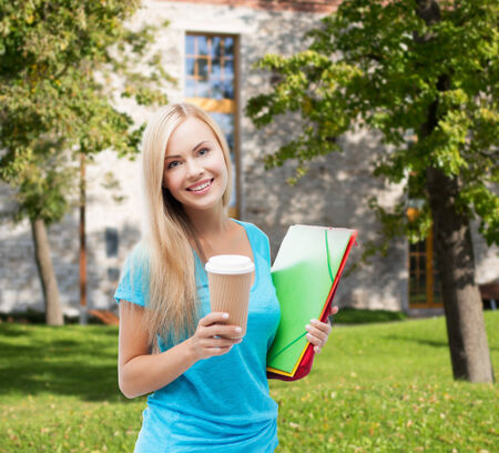 school and education concept - smiling student with folders and cup of coffee photo