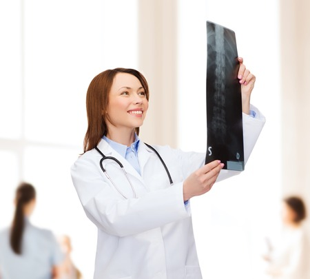 prescribing: healthcare, medicine and radiology concept - smiling female doctor with stethoscope looking at x-ray Stock Photo