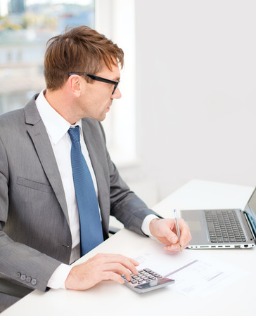 business, office, school and education concept - businessman with laptop computer, papers and calculator Stock Photo - 26175591
