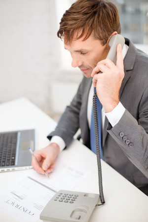 technology, business, internet and office concept - handsome businessman working with laptop computer, phone and documents Stock Photo - 26175593