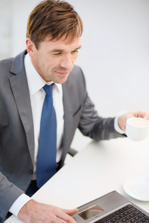 technology, business, internet and office concept - handsome businessman working with laptop computer Stock Photo - 26175555