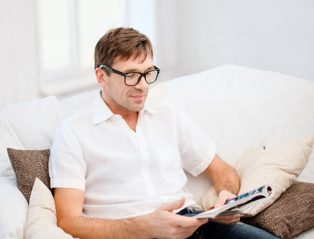 leisure, education and lifestyle concept - man with magazine at home Stock Photo - 26175557