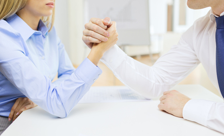 business and office concept - businesswoman and businessman arm wrestling during meeting in office photo