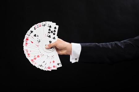 Magia, spettacolo, circo, gioco d'azzardo, casinò, poker, spettacolo concept - stretta di mano mago in possesso di carte da gioco Archivio Fotografico - 26175544