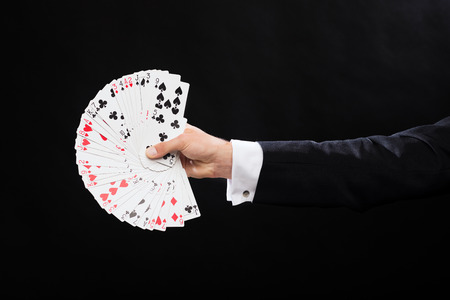 magic show: magic, performance, circus, gambling, casino, poker, show concept - close up of magician hand holding playing cards