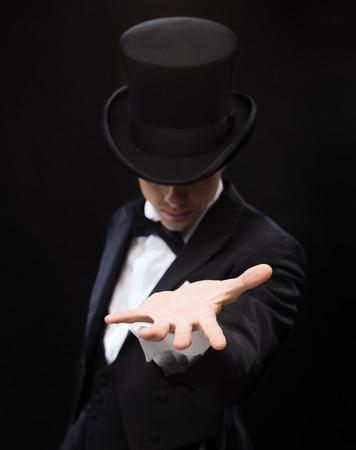 마술, 퍼포먼스, 서커스, 표시 및 광고 개념 - 마술사가 그의 손의 손바닥에 뭔가 들고