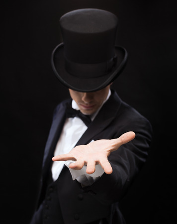 magic, performance, circus, show and advertisement concept - magician holding something on palm of his hand Reklamní fotografie - 26175547