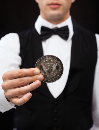 american silver eagle: magic, performance, circus, casino and show concept - casino dealer holding half dollar coin Stock Photo