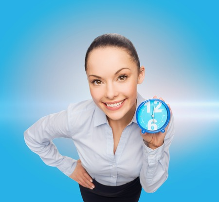 lack of confidence: business, time and deadline concept - smiling businesswoman with blue clock