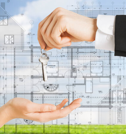real estate, constructure, architecture and develooing concept - close up of man hand passing house keys to woman photo