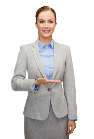 business, future technology and office concept - smiling businesswoman holding something imaginary on palm of her hand photo