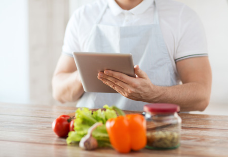 cooking, technology and home concept - closeup of man reading recipe from tablet pc computer photo