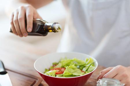 aceite de cocina: cocinar y concepto de hogar - cerca de las manos masculinas aromatizantes ensalada en un bol con el aceite de oliva