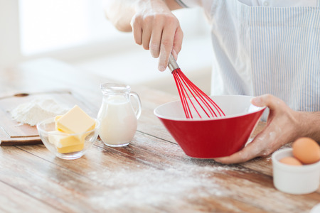 cooking and home concept - close up of male hand whisking something in a bowl photo