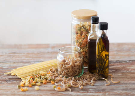 cooking and food concept - close up of two olive oil bottles and pasta in jars photo