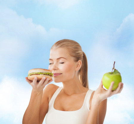 health, diet and food concept - happy woman smelling hamburger and holding apple photo