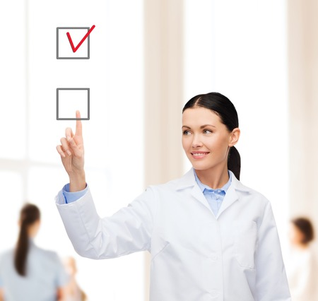 new medicine: healthcare, medicine and technology concept - smiling female doctor pointing to checkbox Stock Photo