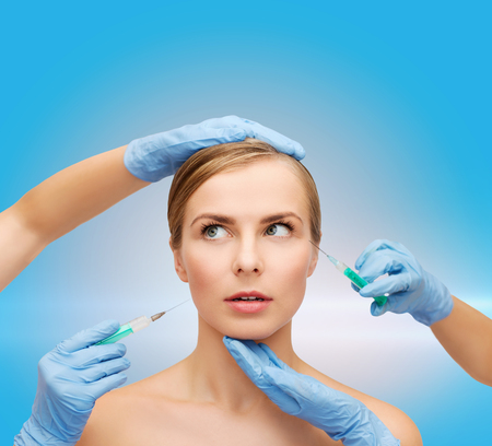 healthcare, beauty and medicine concept - beautiful scared woman face with closed eyes and beautician hands with syringe photo