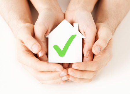 affordable: real estate and family home concept - male and female hands holding paper house with green check mark