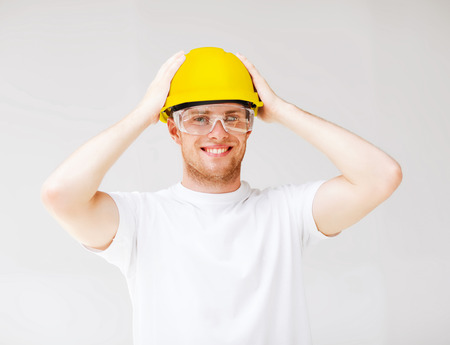 building, developing, consrtuction and architecture concept - picture of male builder in safety glasses and yellow helmet photo