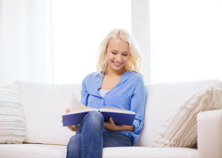 leasure: leasure and home concept - smiling middle-aged woman reading book and sitting on couch at home Stock Photo