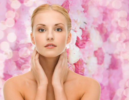 beauty and spa concept - face of beautiful woman touching her face skin photo
